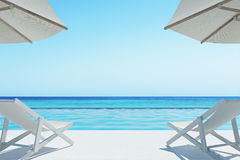 Ocean view with two deck chairs. Two deck chairs are standing under beach umbrellas on an ocean shore. Concept of rest. 3d rendering mock up Stock Photography