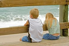 Ocean Watch. Young boy and girl (brother and sister) watching the ocean waves from the boardwalk Stock Photography