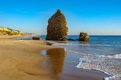 Old ruined defense tower near ocean in the beach. Ocean water, beach and old ruined defense tower stock photo