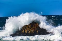 Ocean Water Explosions. Pebble Beach, California, February 19, 2018:  Wave action on a clear and blustery day produces water explosions against the rocky Stock Photo