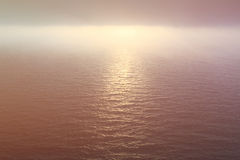 Ocean water and foggy sky at sunset Royalty Free Stock Photos