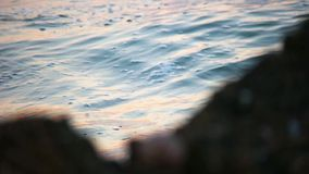 Ocean water moving swiftly with jagged rocks blurred foreground stock footage