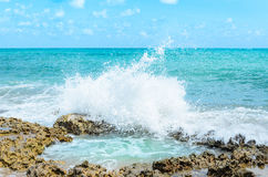 Ocean water splashing on rocks and forming a natural pool in the center of the image Royalty Free Stock Image