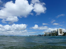 Ocean waters ripple off the coast of waikiki with hotels lining Stock Photo
