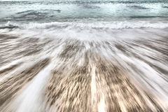 Ocean wave. Rolling onto sandy beach Stock Images