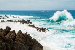 Ocean wave approaching the rock shore Stock Photos