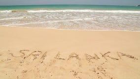 Ocean wave approaching words Sri Lanka written in sand on beach stock video