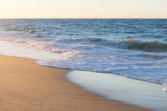 Ocean wave on beach sand in sunset light Stock Images