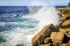 Ocean Wave Breaking on Rocks. A huge wave breaking on the rocks and boulders forming on the coast stock image