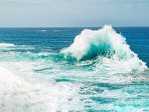 Ocean wave breaking the sea water. Beautiful turquoise ocean wave breaking the sea water, with water foam and blue sea water on the background Royalty Free Stock Photo