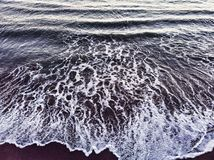 Ocean wave breaks into the coast with backwash royalty free stock image