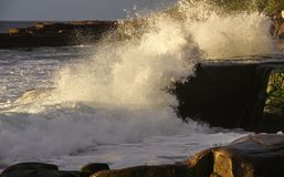 Ocean wave breaks over gleaming rock outcrops Stock Photos