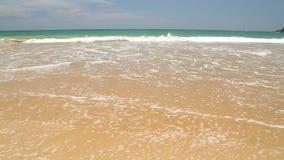 Ocean wave covering words Sri Lanka written in sand on beach stock footage