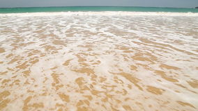 Ocean wave covering words Sri Lanka written in sand on beach stock video