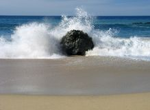Ocean wave crash. A wave crashes on and around a large rock on a beach Stock Photography