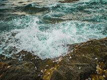 Ocean wave crashing Onto Rocky in the Blue ocean stock photos