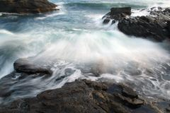 Ocean Wave crashing over multiple rock outcrops. Ocean waving crashing over rocks at payzant campground on the Juan de Fuca backpacking trail, Vancouver Island stock images