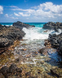Ocean wave crashing through a rocky inlet royalty free stock images