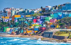 Colorful house line the ocean front in San Juan, Puerto Rico. Ocean and wave don't Match the beauty of the colorful houses going up to Hillside in San Juan Royalty Free Stock Image