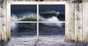 Ocean Wave Flooding. Window frame of beach home with water flooding through and large wave set in background. A concept for the flooding power of the ocean stock photo