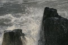 Ocean wave splashing on rock. An ocean wave forcefully splashing around a rock. Great background picture royalty free stock photo