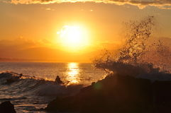 An ocean wave splashes off rocks in golden sunset. Surfers wait for a better wave. Distant hills are lit by the sunlight Stock Photos