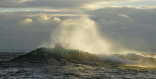 Ocean wave with splashes at sunrise. Against dramatic storm clouds Stock Photography