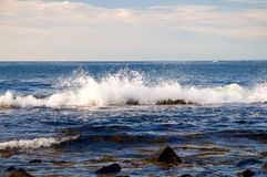 Ocean wave splashing. A view of an ocean wave splashing over rocks on the shore in the early morning sunlight on Mount Desert Island, Maine Royalty Free Stock Image