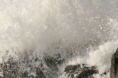 Ocean wave splashing on rock. An ocean wave forcefully splashing around a rock. Great background picture royalty free stock image