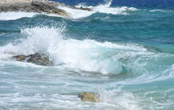 Ocean wave splashing the rocky coast Stock Images