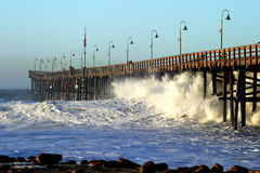 Ocean Wave Storm Pier. Ocean waves throughout at storm crashing into a wooden pier Stock Image