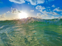 Ocean Wave with Sun, Blue Sky and Clouds royalty free stock photo