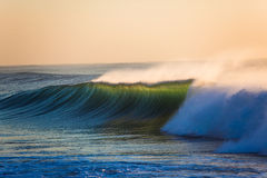 Ocean Wave Sunrise Backlight. Large Indian Ocean wave back light with the sunrise behind giving a display of contrasts as the emerald green wave wall surges and Stock Images