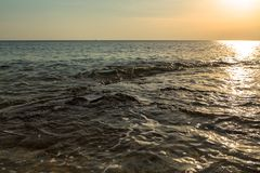 Ocean wave at sunset Stock Photo