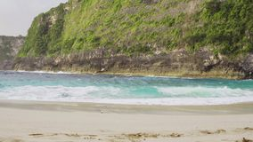 Ocean wave on tropical beach. Kelingking beach Nusa Penida. Ocean wave on tropical beach. White sand and crystal-blue sea. Kelingking beach Nusa Penida stock footage