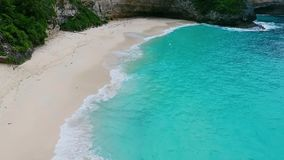 Ocean wave on tropical beach. White sand and crystal-blue sea. Aerial view. Kelingking beach Nusa Penida, Indonesia stock video