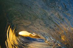 Ocean Wave Tube at Sunset on the Beach in California. An ocean wave breaking on the shore of a beach in Santa Cruz, California during sunset Stock Photos