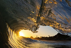 Ocean Wave Tube at Sunset on the Beach in California. An ocean wave breaking on the shore of a beach in Santa Cruz, California during sunset with a small surfer Stock Photography