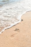 Ocean wave wash away footprints Stock Photos