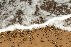 Ocean Wave Washes Over Sand and Pebble Beach Royalty Free Stock Images