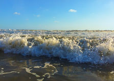 Ocean wave with water curl and foam. Splash of the sea. Sand seashore of tropical beach. Royalty Free Stock Photo