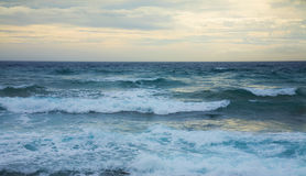 Ocean waves. Partially overcast yellow sky royalty free stock photography