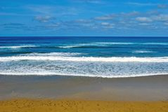 Ocean waves on the beach. Advancing waves at ocean shore, sandy beach, blue sky with clouds Stock Photos