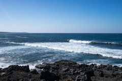 Ocean waves on the black rocky coastline Stock Images