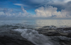 Ocean waves blue with clouds on the sky Stock Image