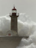 Ocean waves breaking over old pier and lighthouse Royalty Free Stock Images