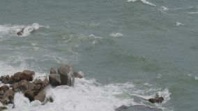Ocean waves breaking on the rocks during a storm. In slow motion stock video