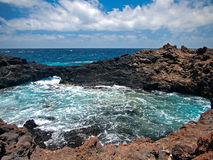 Ocean waves breaking on the rocky coast of hardened lava with caverns and cavities. Blue sky with white clouds and mountains royalty free stock images