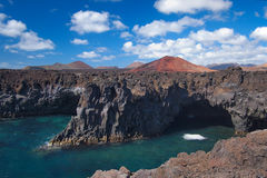 Ocean waves breaking on the rocky coast of hardened lava with caverns and cavities. Deep blue sky with white clouds and mountains. And volcanoes on the horizon stock image
