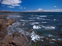 Ocean waves breaking on the rocky coast of hardened lava with caverns and cavities. Deep blue sky with white clouds and mountains Royalty Free Stock Images